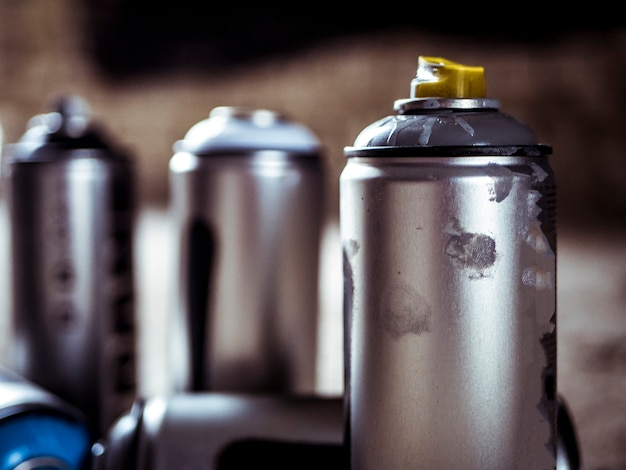 Close macro shot of spray paint cans droped on the dusty ground