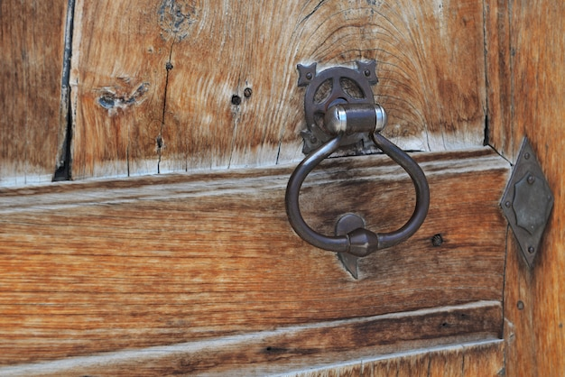 Close on metal  knock on an old wooden door