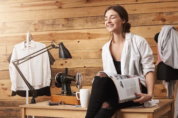 Закрой глаза и увидишь новые идеи. внутренняя съемка счастливой канализации, сидящей на столе, читающей журнал и пьющей чай, перерыв на работу, обсуждение последних сплетен с коллегой девушка и швейная машинка