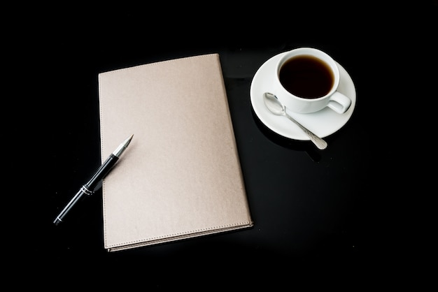 Close notebook, pen and cup of coffee