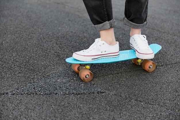 スケートボードに立っている流行に敏感な女性のクローズ