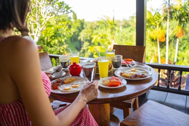 Крупным планом леди держит нож и вилку, сидя за столом с едой и напитками stock photo
