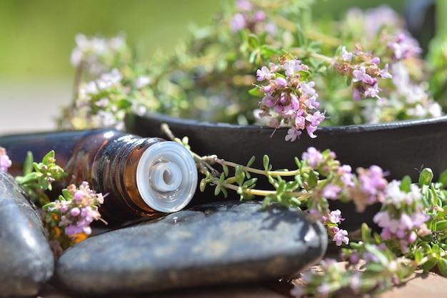 Закройте бутылку эфирного масла, пролитого на камень с ароматными травами