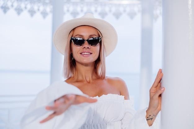 ボリュームのある白いトレンディなトップとクラシックな豪華な帽子とヒョウのサングラスでスタイリッシュな女性の屋外ファッションの肖像画を閉じる