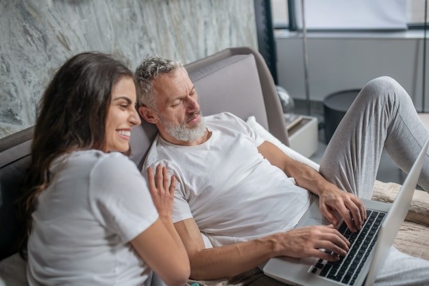 Close people. concentrated gray-haired husband typing on laptop keyboard and joyful laughing wife touching shoulder on bed