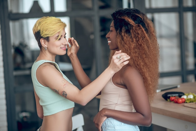 Близкие люди. две молодые радостные улыбающиеся женщины, стоящие напротив касаясь волос друг друга, мило заботятся