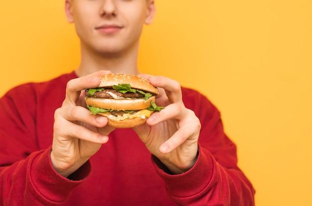 Закрыть фото. мужчина держит в руках вкусный большой гамбургер на желтом.