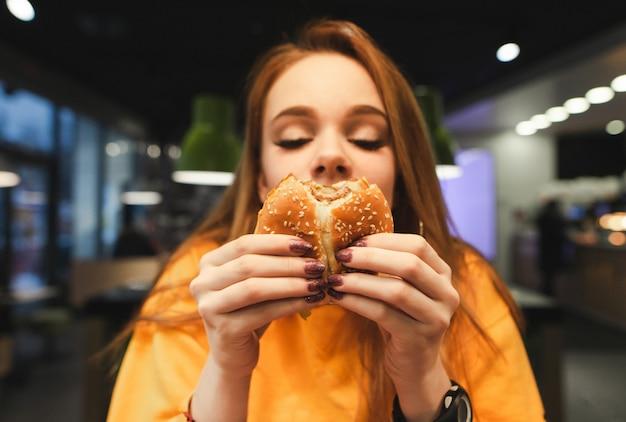 美しい少女とハンバーガーの写真を閉じる
