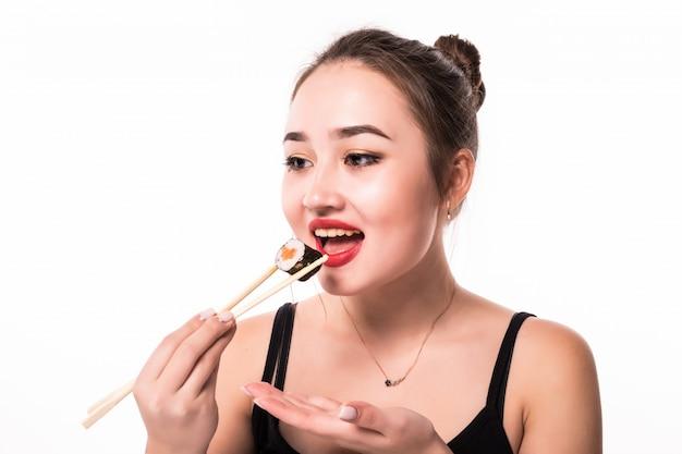 Ritratto vicino di bella donna che mangia i rotoli di sushi