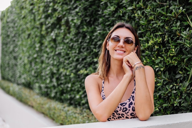 Close portrait of european woman in leopard top and sunglasses and round earings on green bush wall