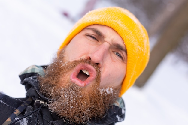 A close portrait of a man with a beard, all face in the snow, in a snowy forest
