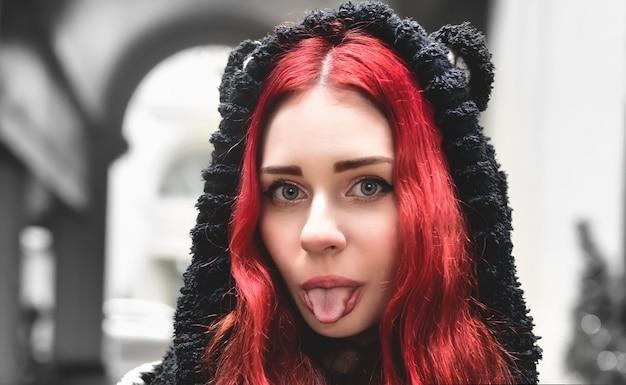 밖에 서 따뜻한 옷에 빨간 머리를 가진 웃는 십 대 소녀의 초상화를 닫고 카메라에 보이는 농담 그녀의 혀를 보여주는.