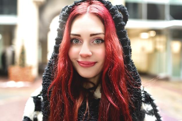 밖에 서 따뜻한 옷에 빨간 머리를 가진 웃는 십 대 소녀의 초상화를 닫고 카메라에 보이는
