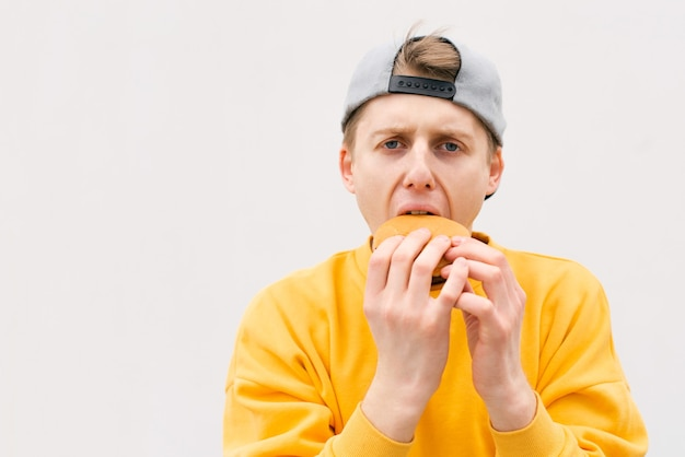 目を閉じてハンバーガーを食べる若い男の近い肖像画