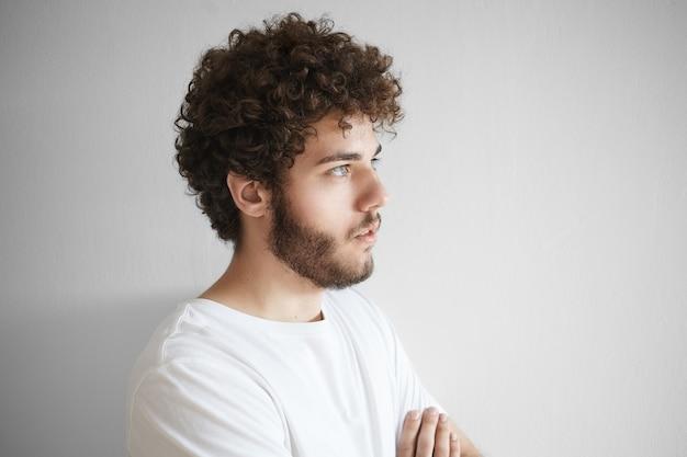 あなたのテキストやプロモーション情報のための空白のコピースペースの壁で隔離されたポーズの巻き毛、太いひげ、美しい特徴を持つ魅力的な若い白人男性の肖像画を閉じる
