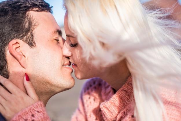 お互いにキスしている美しい白人カップルの近くの肖像画。キスで情熱的なクローズアップ。若い男と女。若い男性と女性のための愛の概念
