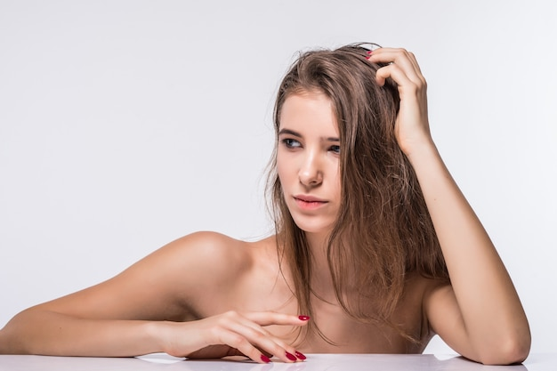 白い背景で隔離のファッションの髪型と服のない豪華なブルネットモデルの女の子の肖像画を閉じる