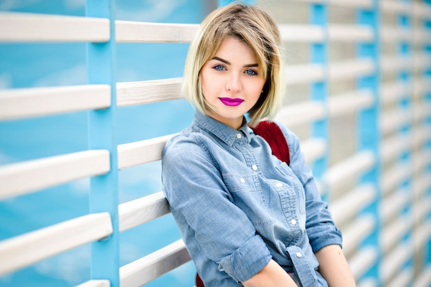 Close portrait of a smiling girl with short blond hair, bright pink lips and nude make up leaning on blue and white stripes fence on the background