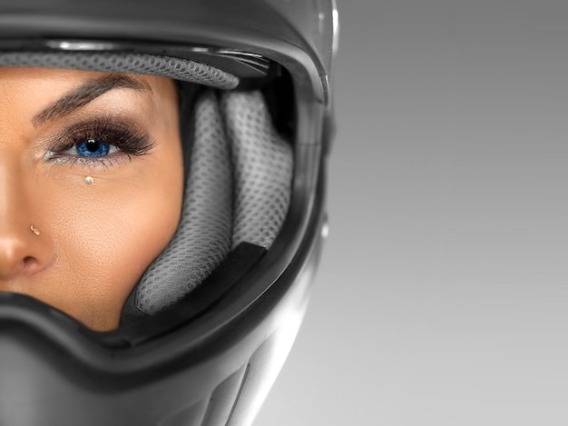 Close portrait of a woman in a motorcycle helmet looking at camera. half face.