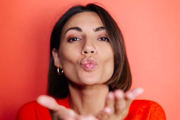 Close portrait of woman on red wall looks to front and sends air kiss