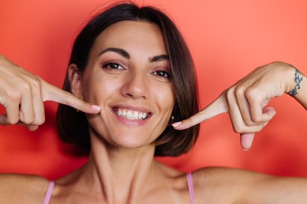 Close portrait of woman on red wall shows points fingers on white teeth smile