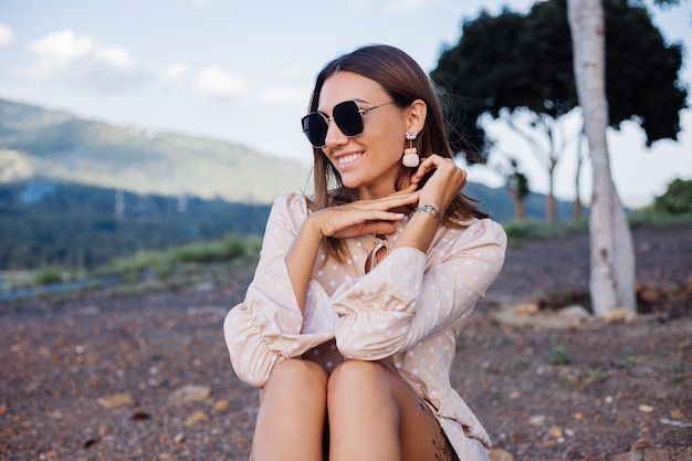 Chiudere il ritratto di giovane donna con occhiali da sole e orecchini al caldo tramonto nel parco