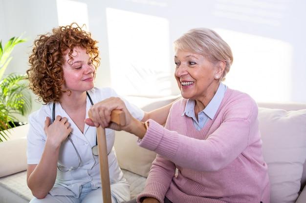 Тесные позитивные отношения между старшим пациентом и лицом, осуществляющим уход. счастливая старшая женщина говоря к дружелюбному попечителю.