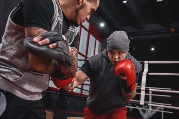 Close quarter boxing strong tattooed athlete in sports clothing training on boxing paws with partner