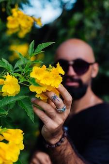 Chiudere il colpo di uomo barbuto abbronzato brutale in occhiali da sole con tatuaggio della palma sul dito si leva in piedi circondato da fiori gialli nel parco