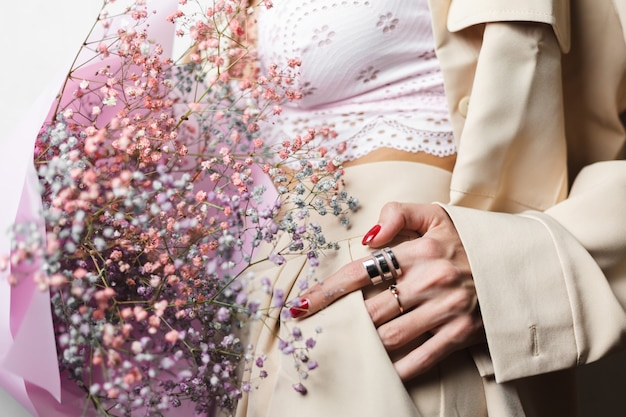 Close shot no head woman in beige suit and white bra hold bouquet of colorful dried flowers red manicure two rings on fingers
