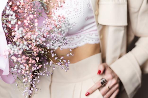 베이지 색 양복과 흰색 브래지어에 가까운 총 머리 여자가 손가락에 다채로운 말린 꽃 빨간 매니큐어 두 반지의 꽃다발을 개최