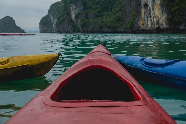 遠くに山のある水に赤いカヌーのショットを閉じる