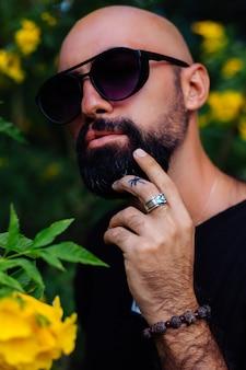 손가락에 야자수 문신을하는 선글라스에 잔인한 검게 그을린 수염 난 남자의 총을 닫습니다 공원에서 노란색 꽃으로 둘러싸인 스탠드