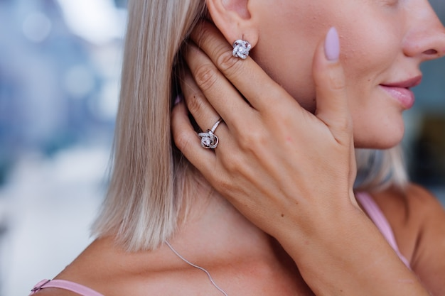 손가락에 귀걸이와 반지를 착용 드레스 손과 귀에 풍부한 고급 여자의 닫기 샷