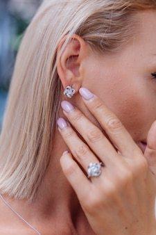 Крупным планом - богатая роскошная женщина в платье, рука и ухо с серьгами и кольцом на пальце