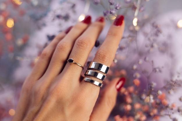 2つのリングを身に着けている女性の手の指のクローズショット