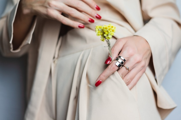 Крупным планом женщина руки красный маникюр два кольца в бежевом костюме. желтый милый засушенный цветок в кармане.