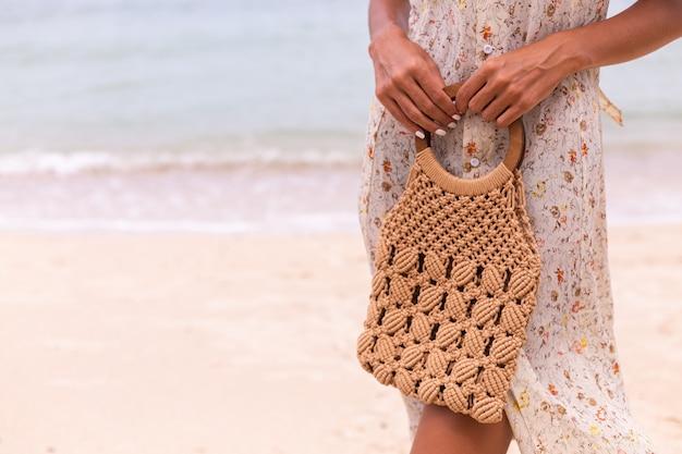 가벼운 여름 비행 드레스 해변, 배경에 바다에 니트 가방을 들고있는 여자의 총을 닫습니다.