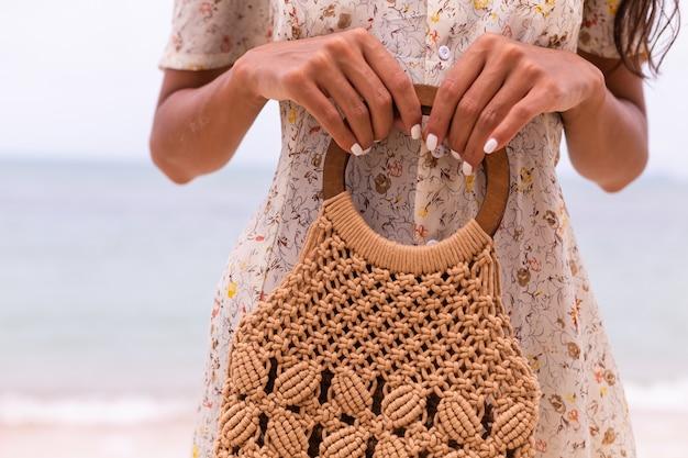 Крупным планом женщина в легком летнем летающем платье держит вязаную сумку на пляже, море на фоне.