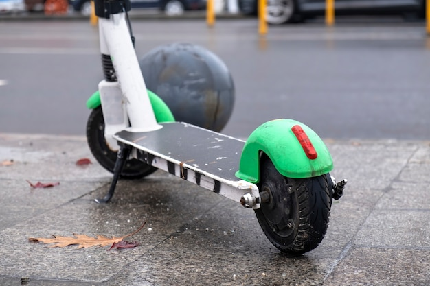 Close shot of a parked electric scooter near the road with moving cars, wet and cloudy weather in bucharest, romania