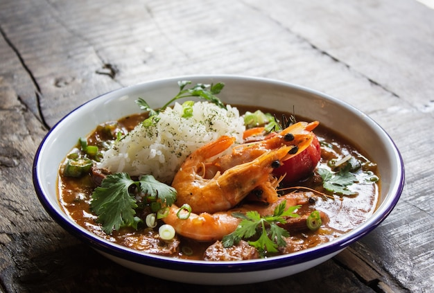 Close shot of soup with shrimps, rice, and vegetables leaves in a bowl on a wooden surface