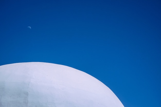 Close shot of the top of the white concrete round building with clear blue sky in the background