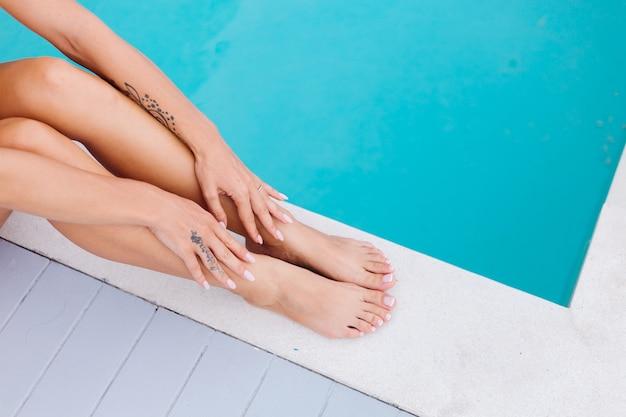 총 여자 발과 손을 닫습니다. 여자 휴가에 파란 수영장의 가장자리에 앉아