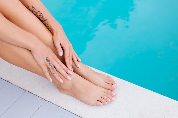 Mani e piedi di donna colpo vicino. la donna si siede sul bordo della piscina blu in vacanza