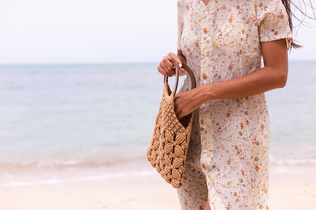 Close shot of woman in light summer flying dress holding knitted bag on beach, sea on background.