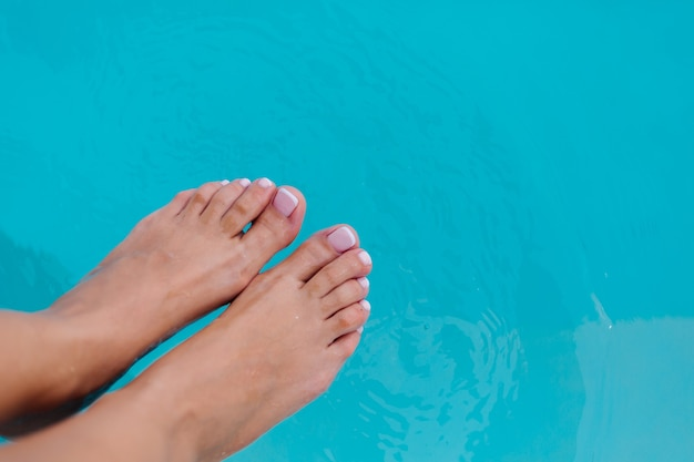 Close show of womans feet with french pedicure gel polish on background of blue water in swimming pool.