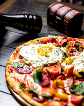 Close side view mixed pizza with tomatoes olives bell pepper eggs sausages on the board a book a knife and a fork on the table