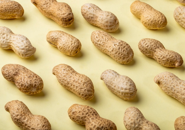 Close side view peanuts in shell on a yellow background