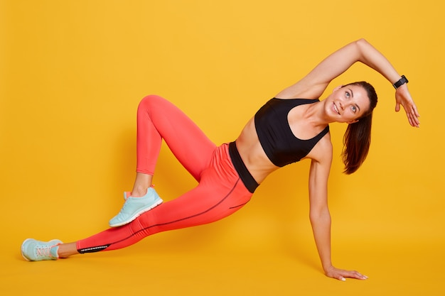Close sporty young woman doing sport exercises isolated on yellow, wearing stylish sportwear. concept of healthy life and natural balance between body and mental development.