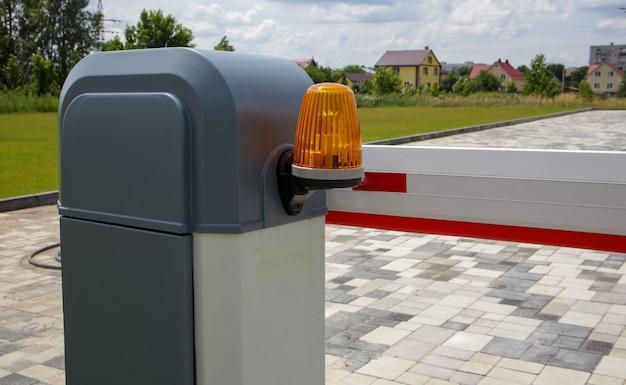 Закрыть ворота. автоматическая система безопасности. автоматическая система входа. желтый световой сигнал с уличным шлагбаумом. шлагбаумные ворота автоматическая система безопасности.
